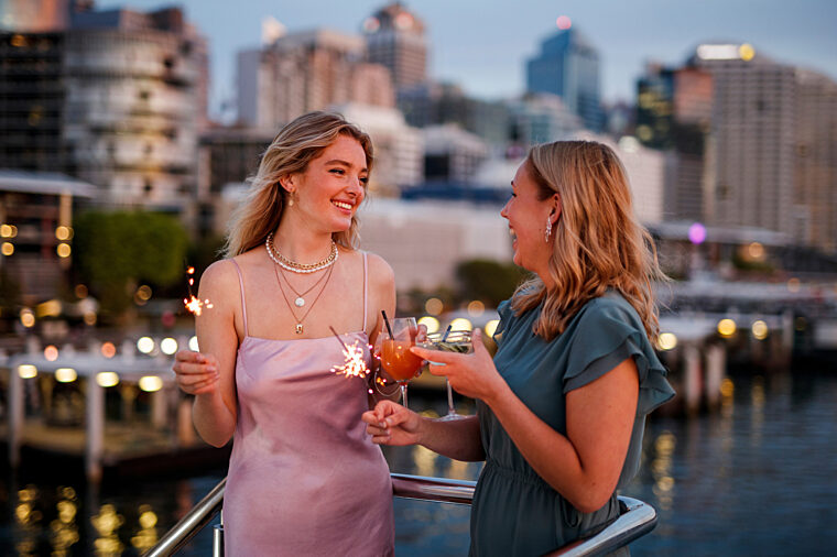 Two girls celebrating with cocktail drinks outdoors with Darling Harbour in the background