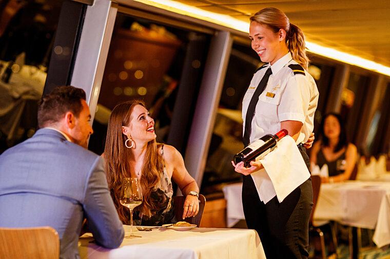 Gold Penfolds Dinner couple having degustation menu, waitress presenting St Henri wine to dining table drinks and glasses