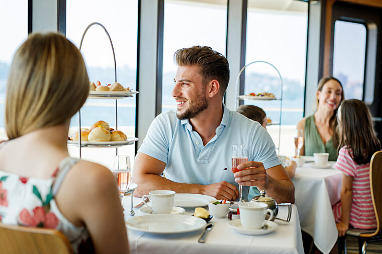 Couple eating High Tea at Sea and enjoying the views drinking pink bubbles
