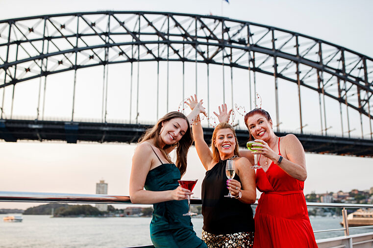 Smart casual group of girls celebrate Special Events on open deck with Harbour Bridge in the background
