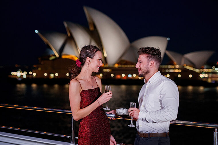 Young couple having drinks celebrating anniversary Gold Penfolds champagne night time Opera House