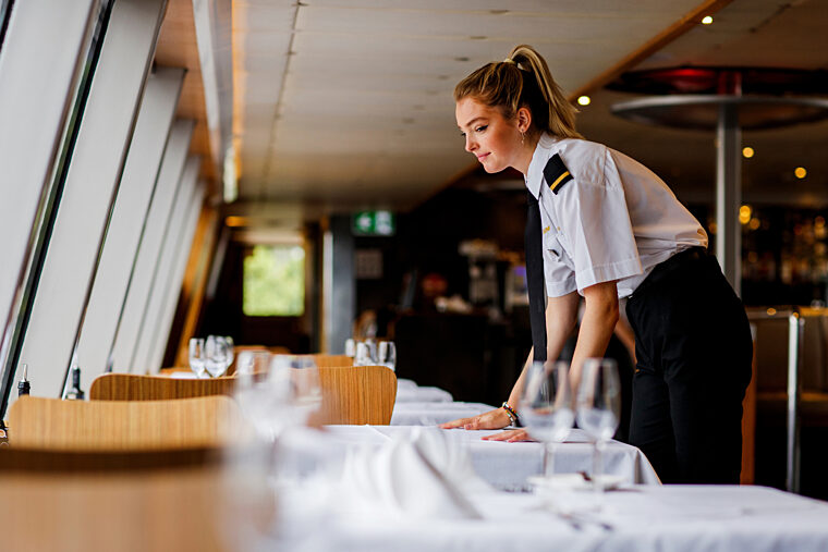 Waitress crew setting dining table for Gold Penfolds Dinner onboard Sky Deck