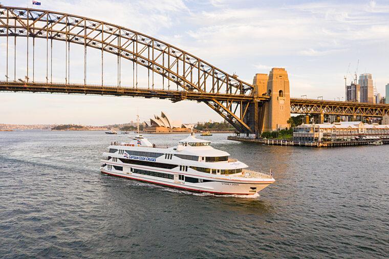 Sydney 2000 boat cruising past Harbour Bridge