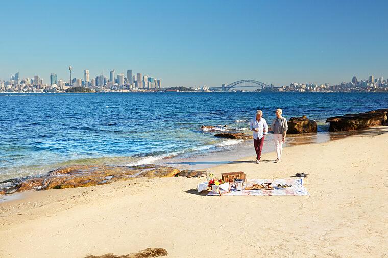 Senior couple walking on the beach in Shark Island ferry sightseeing HOHO non-ccc dnsw