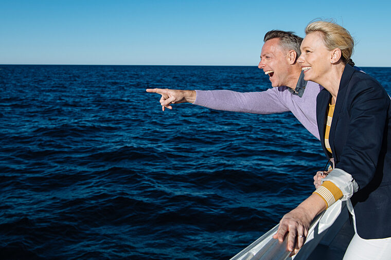Couple spotting whales on open water sightseeing wildlife non-ccc dnsw