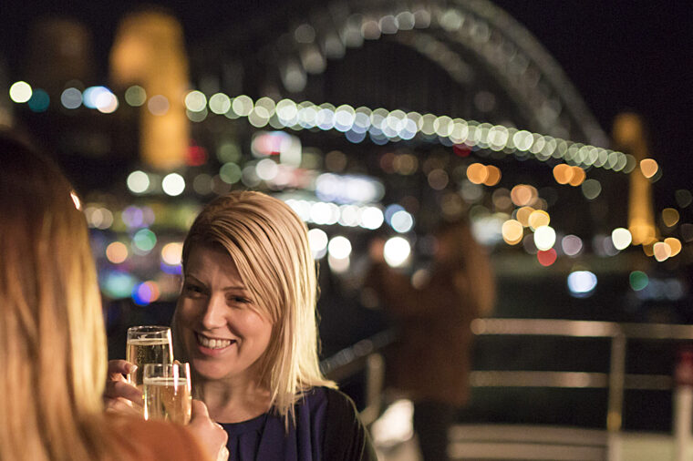 Friends girls having champagne on open deck with Harbour Bridge night lights in the background special events