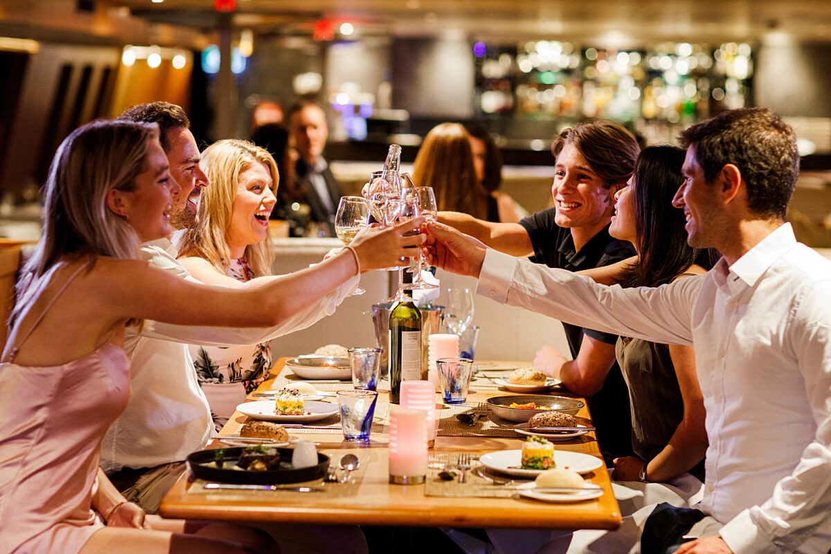 Group having dinner on Sky Deck cheers wine, dine and drinks