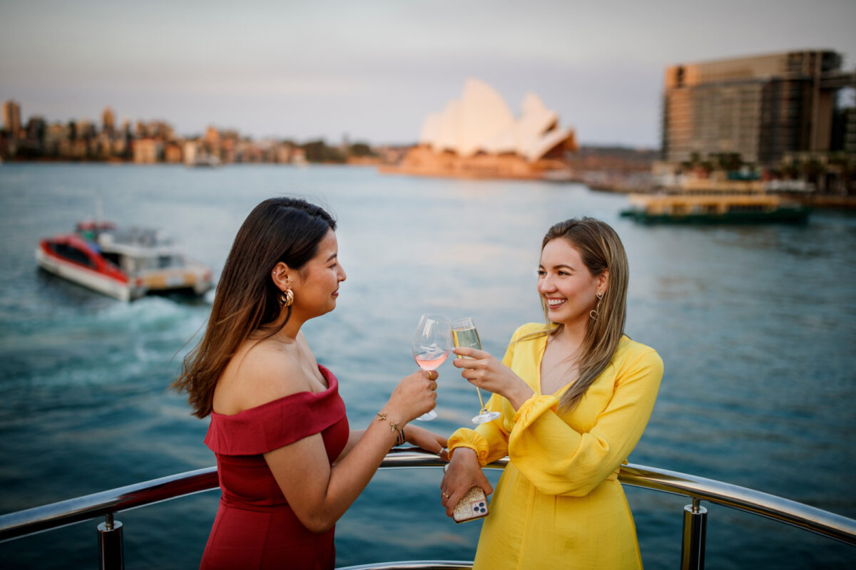 Two girls toasting champagne flute with Opera House and Rocket ferry in the background